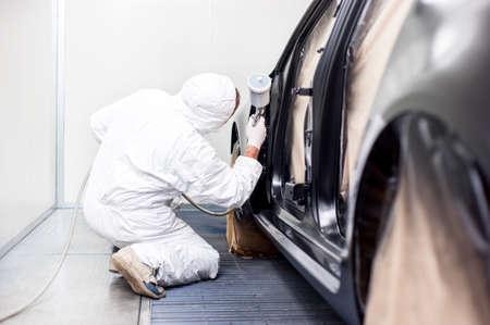 Trabalhador que pinta um carro em uma caixa especial pintura, vestindo um traje branco e um capacete de respira Banco de Imagens