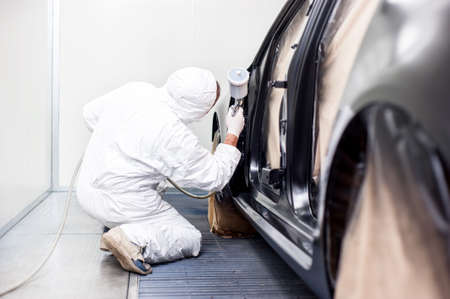 auto garage: worker painting a car in a special painting box, wearing a white costume and a breathing helmet as protection gear