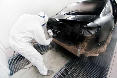 Trabalhador que pinta um carro na garagem usando uma arma airbrush