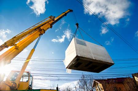 camion grua: Grúa industrial que opera y el levantamiento de un generador eléctrico de la luz solar y el cielo azul Foto de archivo