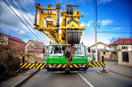 Industrial mobile crane with hydraulic and telescopic rack operating on work construction site  photo
