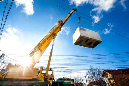 lifting: Mobiele kraan bedienen door het optillen en verplaatsen van een zware elektrische generator Stockfoto