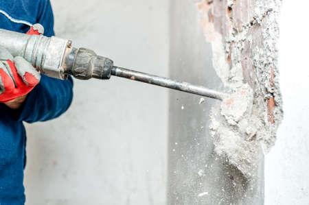 hombre usando un martillo neumático para perforar en la pared. trabajador profesional en el sitio de construcción Foto de archivo