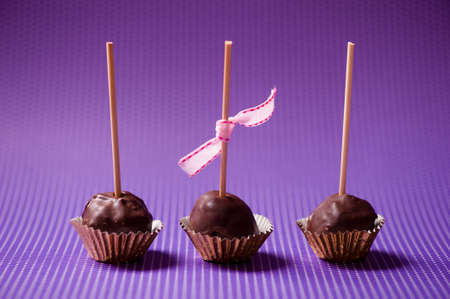 one-bite crunchy and creamy chocolate cupcakes isolated on purple background  photo