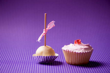 cupcake and muffin in a pastry isolated on purple background photo