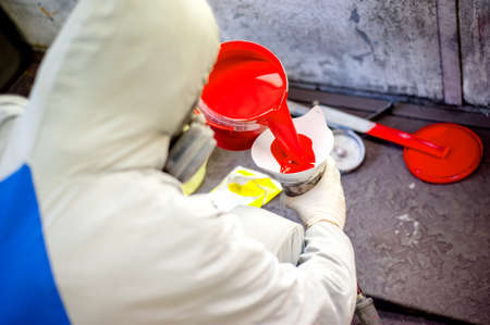 shop skill: Auto mechanic mixing and pouring red paint for spraying and painting cars in industrial factory