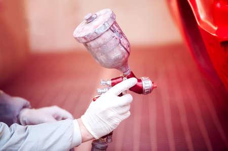 Ouvrier peignant un véhicule rouge dans la cabine de paiting utilisant des outils professionnels et pistolet Banque d'images