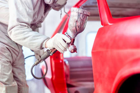 paint gun: Professional worker spraying red paint on a car body Stock Photo