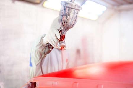 garage automobile: Close-up de pistolet et travailleur peindre une voiture Banque d'images