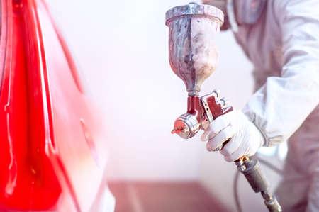 body paint: Primer plano de la pistola con pintura roja que pinta un coche en el stand especial Foto de archivo