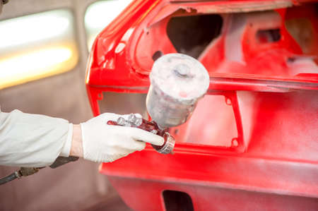 paint gun: Close-up of spray paint gun painting a red car in painting booth