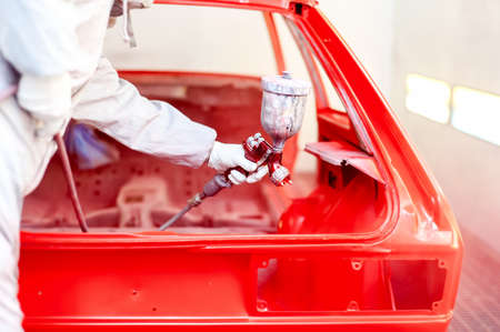 paint box: Close-up of spray paint gun with worker working on a red car Stock Photo