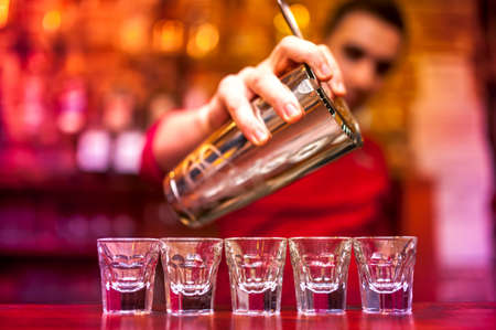 shooter drink: Bartender pouring strong alcoholic drink into shots at nightclub