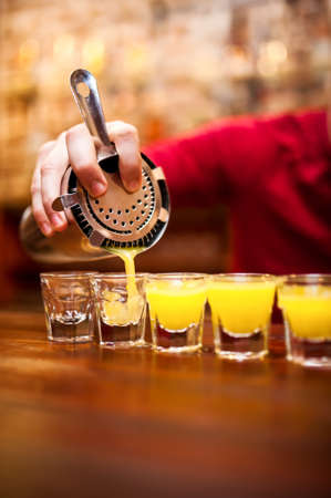 alcoholic drink: Bartender pouring strong alcoholic drink into small glasses on bar