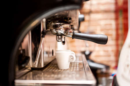 with coffee maker: machine preparing espresso in coffee shop or bar