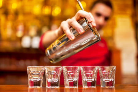 shooter drink: Close-up of bartender hand pouring alcoholic drink in nightclub, pub or bar