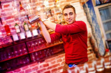 nightclub bar: barman using a shake mixer cocktails and drinks in nightclub, bar or pub
