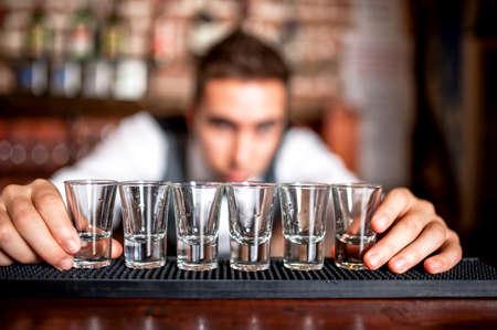bartender preparando e forro copos de shot de bebidas alco Banco de Imagens