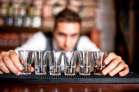 distilled alcohol: bartender preparing and lining shot glasses for alcoholic drinks on bar
