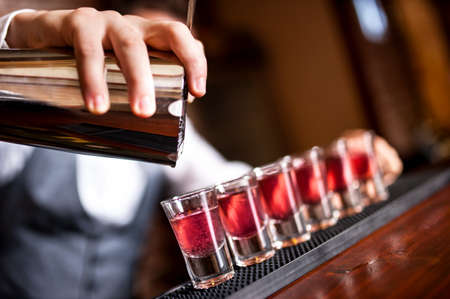 distilled: close-up of barman hand pouring alcohol into shot glasses in a nightclub or bar