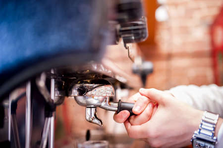 espresso machine: barman using a tamper and making espresso coffee