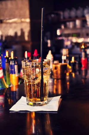 energic alcoholic beverage on bar with straw and wiskey with  nightclub background photo