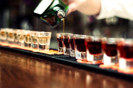 Barkeeper gießt alkoholisches Getränk in kleine Gläser auf bar Lizenzfreie Bilder