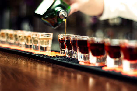 tomando alcohol: Bartender derrama bebidas alcohólicas en vasos pequeños en la barra de