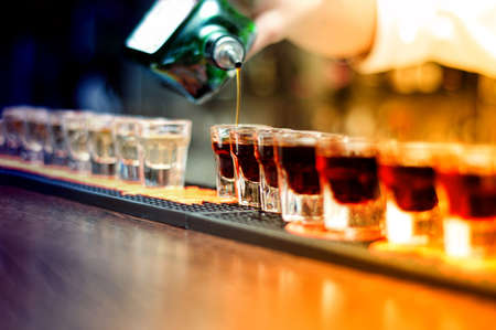 Bartender pouring strong alcoholic drink into small glasses on bar, shots Stock Photo