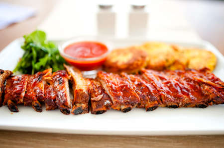 spare ribs: main dish - pork ribs and barbeque sauce with parsley and bread Stock Photo