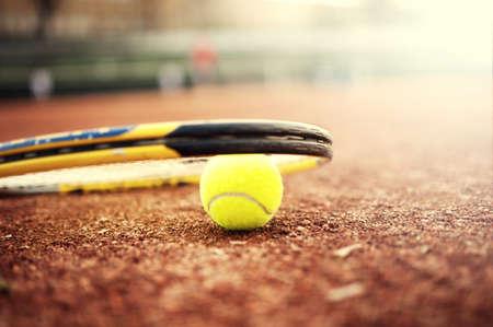 tennis racket: primer plano de una pelota de tenis y la raqueta en la cancha de arcilla, día de verano en el tenis
