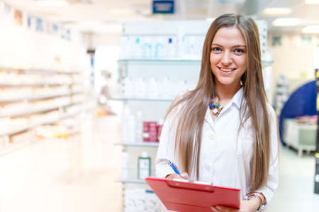 pharmacy store: portrait of smiling young blonde pharmacist at drug store with red clipboard  Stock Photo