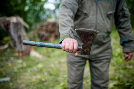 Dangerous man holding an custom made steel, sharp axe in the woods photo