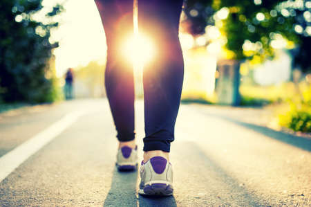 Close-up of woman athlete feet and shoes while running in park  Fitness concept and welfare with female athlete joggin in city park Stock Photo
