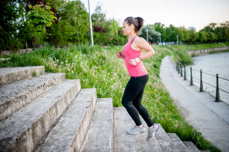 healthy lifestyle sports woman running on street stairs along river Stock Photo