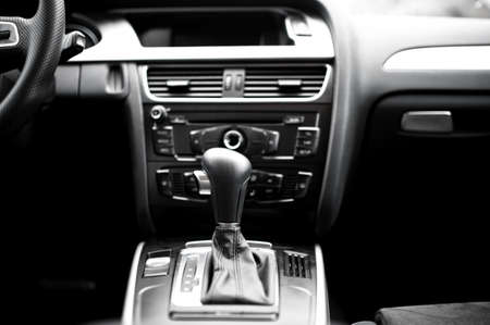 Interior details and elements of modern car, close-up of automatic gearshift knob with cockpit background photo