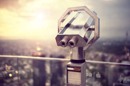 admire: Binoculars or telescope on top of skyscraper at observation deck to admire the city skyline at sunset  Vintage effect