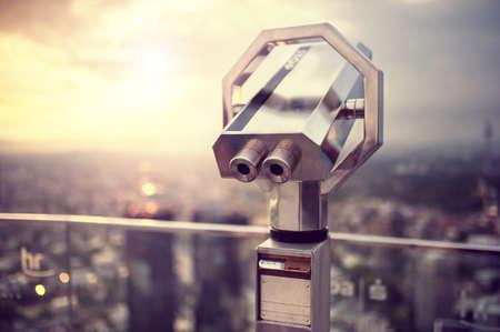 Verrekijker of telescoop op de top van de wolkenkrabber op observatiedek op de skyline van de stad bij zonsondergang Vintage effect bewonderen