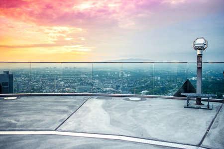 bewonderen: hand gehouden Verrekijker of telescoop op de top van de wolkenkrabber op observatiedek op de skyline van de stad bij kleurrijke zonsondergang te bewonderen