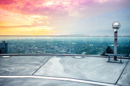 hand held Binoculars or telescope on top of skyscraper at observation deck to admire the city skyline at colorful sunset