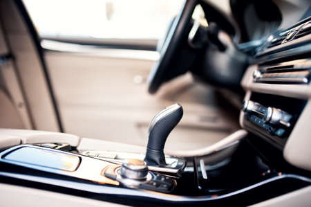 Modern beige interior of new car, close-up details of automatic transmission and gearstick against steering wheel background and dashboard photo