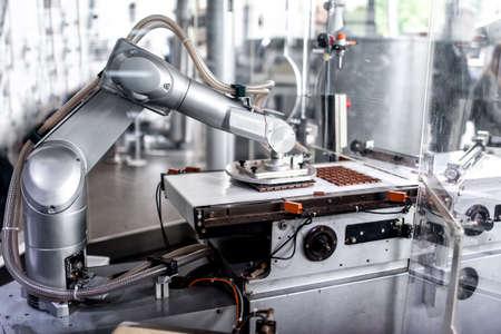 Mano robótica automática el movimiento y preparación de pequeños trozos de chocolate en la fábrica de chocolate fábrica de chocolate industrial con mano robótica automática Foto de archivo