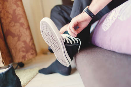 Modern hipster wedding, groom wearing sneakers instead of classic elegant shoes, tying the laces and preparing  Vintage effect on dressing event photo