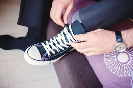Modern hipster wedding, groom wearing sneakers instead of classic elegant shoes, tying the laces  Vintage effect on dressing event photo