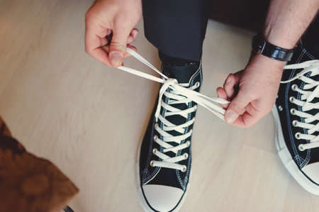 lacing sneakers: Modern hipster wedding, groom wearing sneakers instead of classic elegant shoes, tieing the laces and preparing  Vintage effect