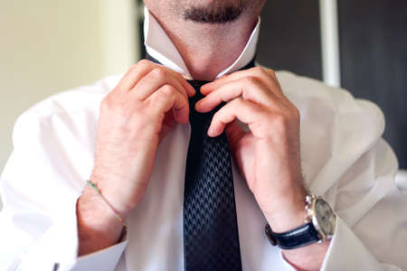 Business man fixing black tie on white shirt  Groom on wedding day fixing tie, vintage effect Stock Photo - 29107615