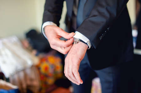 Close up of elegant man, groom hands with suits, ring, necktie and cufflinks on wedding day photo