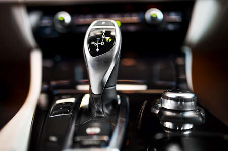 Detail of an automatic gear shifter in a new, modern car  Modern car interior with close-up of automatic transmission and cockpit background