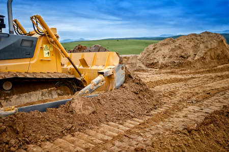 leveling: Heavy bulldozer and excavator loading  and moving red sand or soil on road construction site
