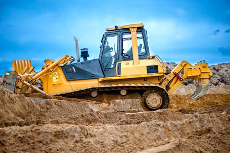 power shovel: bulldozer or excavator working with soil on construction site of building, road or industrial hall Stock Photo